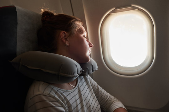 Girl sleeping on a plane. Passenger sleeping in an airplane on an inflatable pillow.
