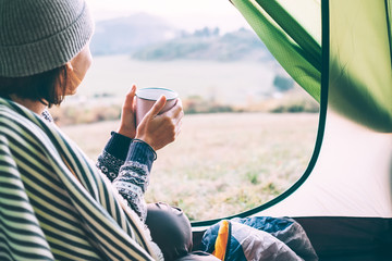 Woman with cup of hot tea sit in camping tent