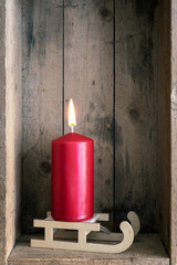 Christmas decoration red candle on a sledge in a wooden box background