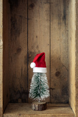 Christmas decoration Santa Claus hat and tree in a wooden box background