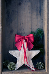 Christmas decoration red ribbon on a star in a wooden box background