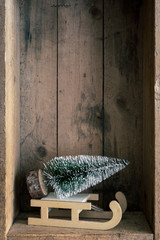 Christmas decoration sledge and tree in a wooden box background