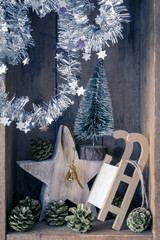 Christmas decoration golden bell jar, sledge, star and tree in a wooden box background