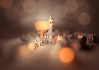 A festive christmas village centre with a church on christmas eve with glowing street lights and decorations. 3D illustration.