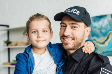 happy young father in police uniform carrying his little son and looking at camera