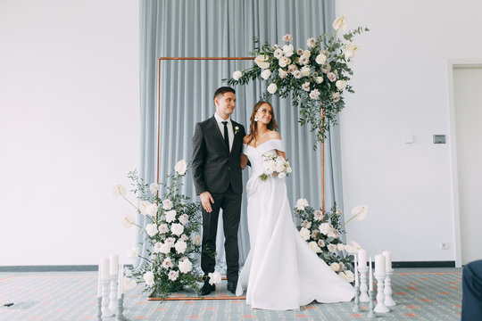Stylish European wedding ceremony. The bride and groom are surrounded by guests. Arch and decor of fresh flowers. .Wedding ideas