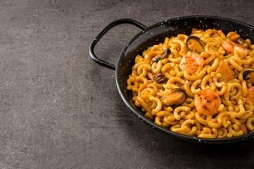 Traditional Spanish fideua. Noodle paella on black stone. Copyspace