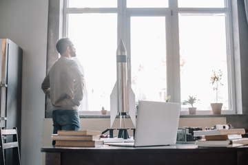 pensive engineer looking at window, rocket model on tabletop at home