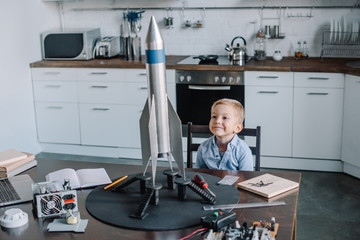 cheerful adorable boy sitting at table with rocket model in kitchen on weekend