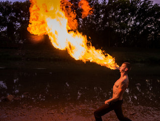 Man fire-eater blowing a large flame