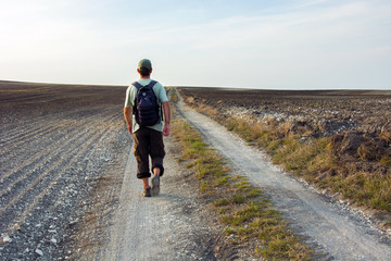 Male traveler with a backpack walking down a dirt road