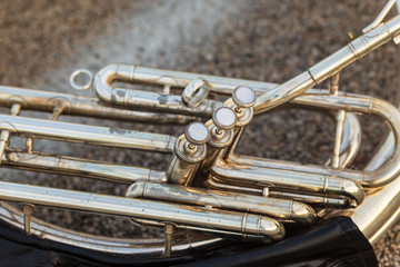 close up of the keys of a sousaphone resting on the ground during a marching band rehearsal