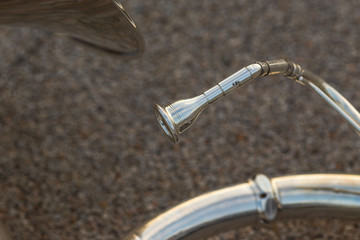 close up of the mouthpiece of a sousaphone resting on the ground during a marching band rehearsal