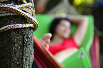 The girl is resting in a hammock.