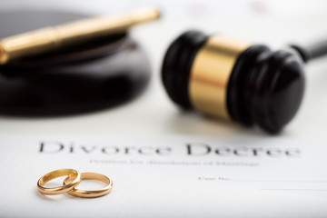 Divorce decree, gavel and wedding rings.