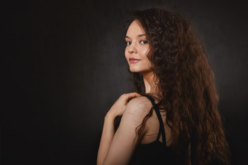 Hair care, beauty and fashion concept. Studio shot of amazing beautiful young brunette lady with charming smile and long healthy hair, promoting shampoo or conditioner at black copyspace wall