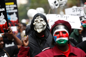 People wearing masks attend a protest calling the Kenyan government and banks to freeze ill-gotten South Sudanese assets and funds, in Nairobi