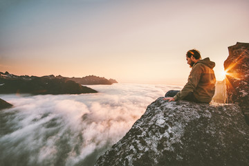Man thinking sitting alone on cliff edge mountain top above clouds travel adventure lifestyle solitude emotions survival extreme vacations