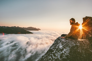Obraz Man relaxing alone on the edge cliff  mountain above clouds travel adventure lifestyle harmony with nature vacations in Norway - fototapety do salonu