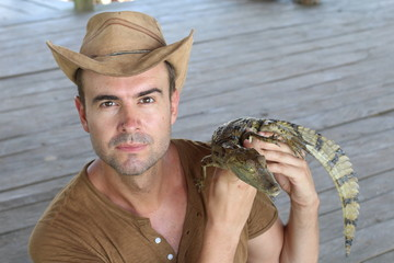 Handsome man holding a caiman