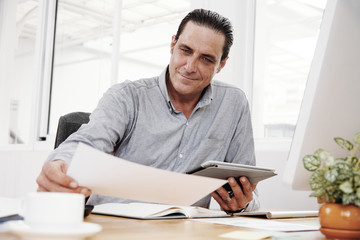 Confident enterpreneur examining contract and using digital tablet during work day at office