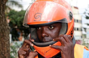 A motorcycle taxi driver known as boda-boda, wears a SafeBoda helmet in Kampala