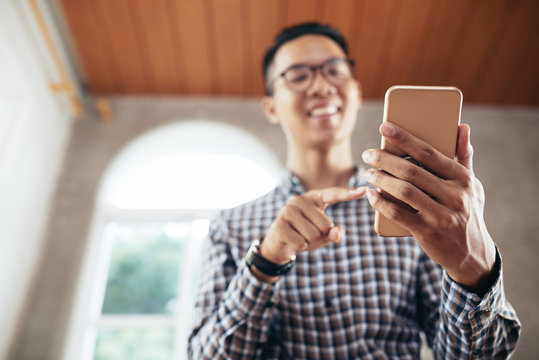 Low angle view of defocused young Asian man smiling cheerfully while taking selfie on modern smartphone