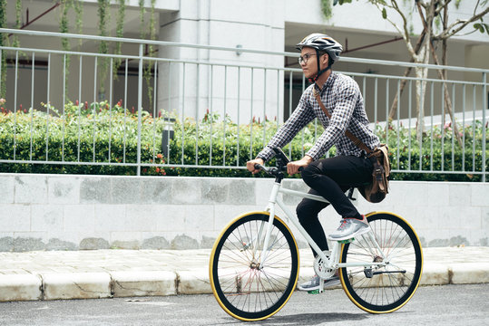 Young Asian man wearing casual clothes, glasses and safety helmet riding bicycle along the road while going home after university
