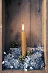 Christmas decoration orange bee wax candle in a wooden box background