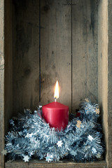 Christmas decoration red candle in a wooden box background