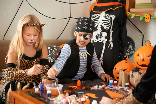 Concentrated Little Children In Beautiful Halloween Costumes Sitting