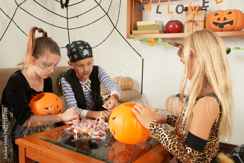 Children with painted faces in Halloween outfits taking lollipops after  trick-or-treating while sitting in beautifully decorated room