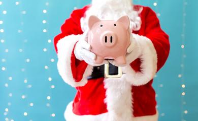 Santa holding a piggy bank on a shiny light blue background