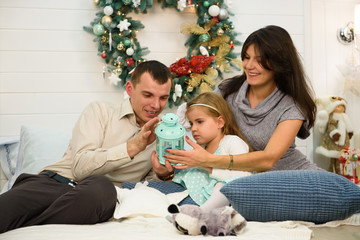 Happy family portrait on Christmas, mother, father and child sitting on bed and lighting a candle at home, chritmas decoration around them