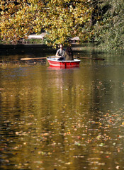 Autumnal trees are pictured as people use a boat at Tiergarten park in Berlin