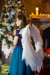 Girl in a blue dress with white wings as an angel stands at the Christmas tree