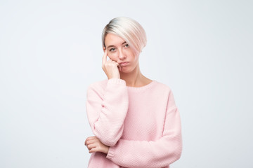Pretty caucasian woman in pink sweater bored, tired with studies in college