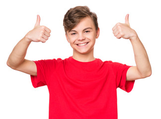 Emotional portrait of caucasian smiling teen boy making thumbs up gesture. Handsome funny teenager...