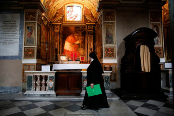 A nun walks past a chapel where a missal that belonged to El Salvador's Archbishop Oscar Romero is exhibited in the Basilica of Saint Bartholomew, in Rome