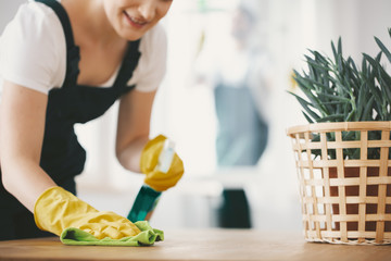 Close-up on smiling housewife with yellow gloves cleaning table with cloth