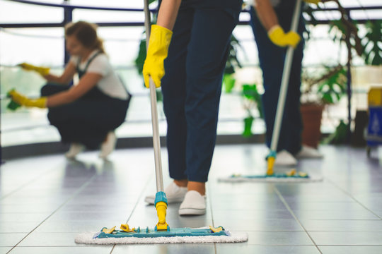 Close-up on professional cleaner with yellow gloves and mop wiping the floor