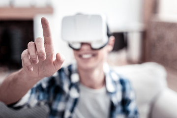 Wonderful gadget. Excited young man wearing virtual reality glasses and smiling while touching a transparent screen