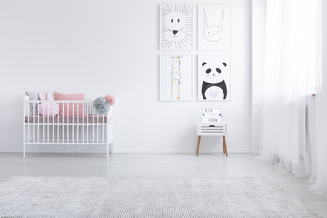 Pink pillow in cradle and posters on the wall in white child's room interior with carpet. Real photo
