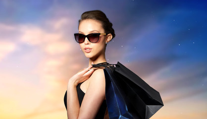 sale, fashion, people and luxury concept - happy beautiful young woman in black sunglasses with shopping bags over sky background