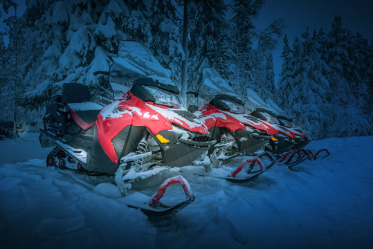 Polar night landscape with row of red snowmobiles