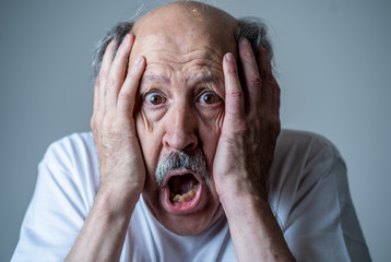 Close up of scared and shocked senior man gesturing in fear with hands and face