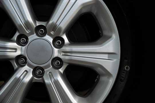 closeup alloy car wheels with soft-focus and over light in the background