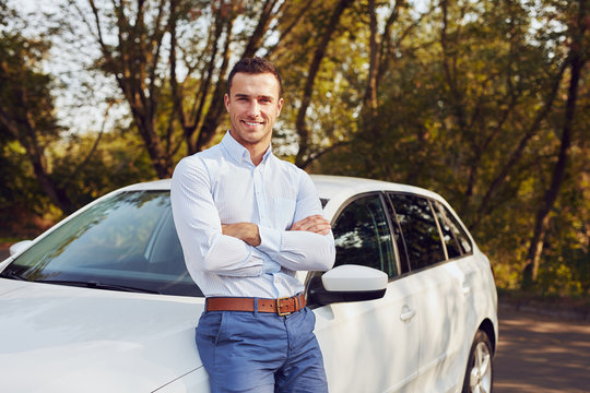 A smiling man with crossed arms stands in front of his new car