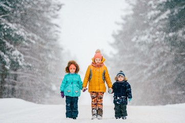 Three funny little children holding hands and standing on road near wood in winter stormy snowy weather. Two girls with boy outdoor nature portrait on abstract background.  Caution - kids on road.