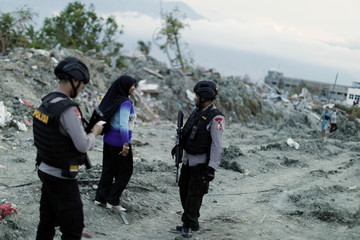 Members of the Indonesian special operations Mobile Brigade Corps patrol Petobo neighborhood hit by the earthquake and liquefaction in Palu